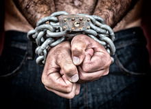 Chained Hands Of An Adult Shirtless Man