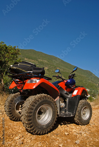Red quad in the countryside and blue sky in the background