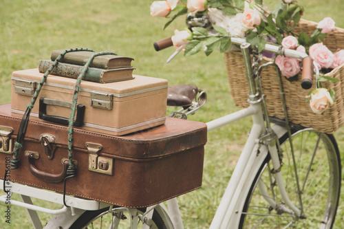 Fotobehang Fiets Vintage bicycle on the field with a basket of flowers and bag