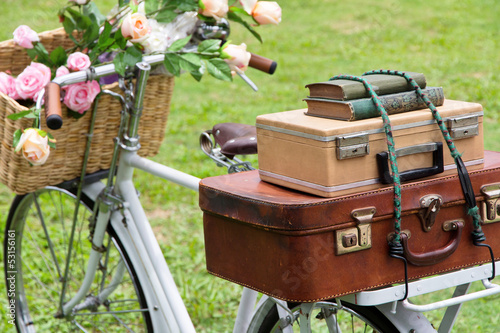 In de dag Fiets Vintage bicycle on the field with a basket of flowers and bag