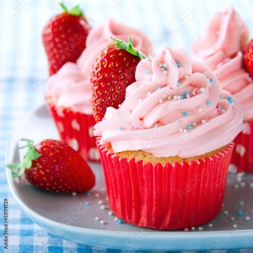Photo  Pink cupcakes with fresh strawberries and sprinkles