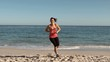 Cheerful brunette working out on the beach