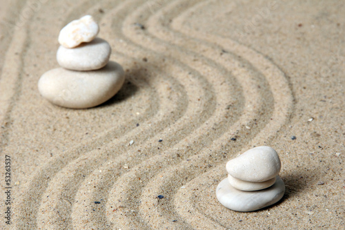 Tuinposter Stenen in het Zand Zen garden with raked sand and round stones close up