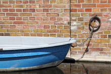 Ein Blaues Ruderboot An Einer Wand Angedockt