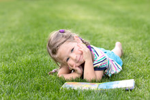 Adorable Little Girl Reading Book In The Green Grass