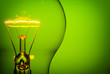 canvas print picture - Close up glowing light bulb on green background