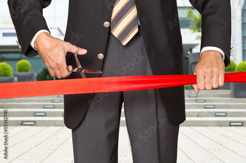 Fotografia  Einweihung - Geschäftsmann durchschneidet rotes Band