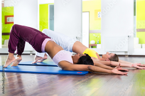 women in the gym doing yoga exercise for fitness #53363147