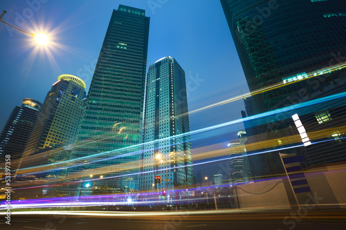The highway car light trails of modern urban buildings Poster