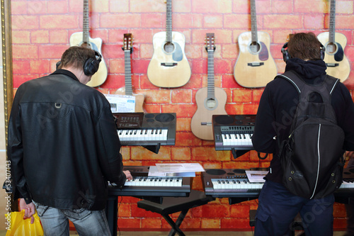 Photo Stands Music store People playing the keyboards with headphones