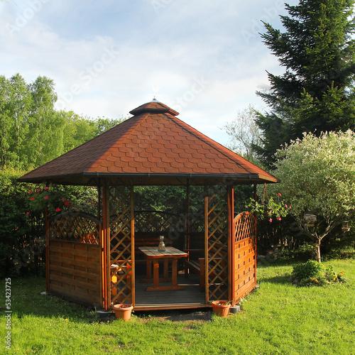 Fotografia  Wooden summerhouse is in a morning garden