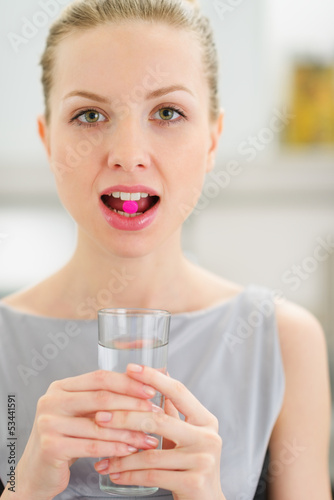 Fototapeta Young woman with pill in mouth obraz na płótnie