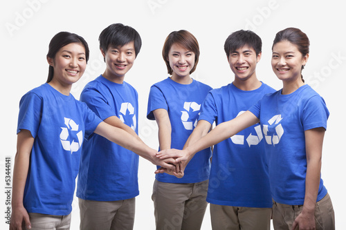 Fotografie, Obraz  Five young people in recycling t-shirts with hands together, studio shot