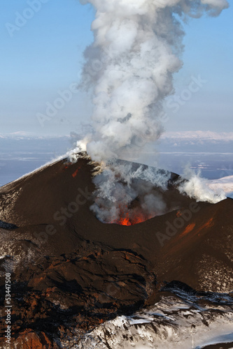Poster Volcano Stunning scenery eruption volcano landscape of Kamchatka Peninsula: aerial view of active volcano, erupting fountain of red hot lava from cinder cone of volcanic crater.