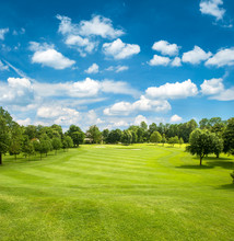 Green Golf Field And Blue Clou...