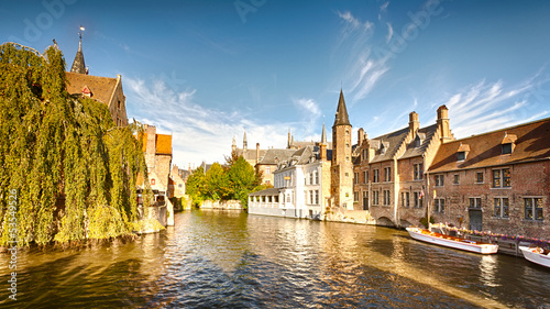 Foto op Canvas Brugge A wide water canal with old buildings