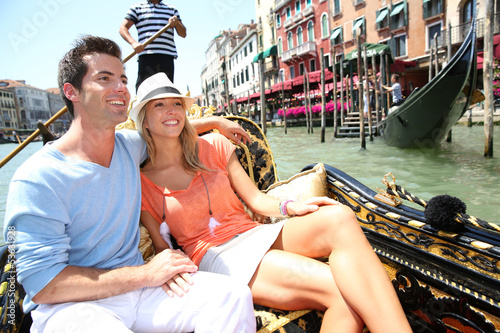Spoed Foto op Canvas Gondolas Couple in Venice having a Gondola ride on canal grande