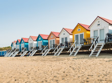 Row Of Colorful Beach Huts In The Sand
