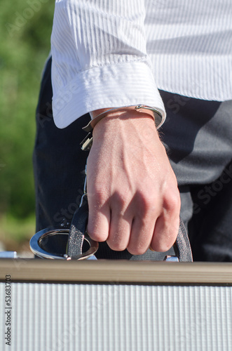 фотография  Close up view of male hand enchained to suitcase