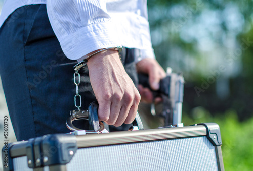 Close up view of male hand enchained to suitcase плакат