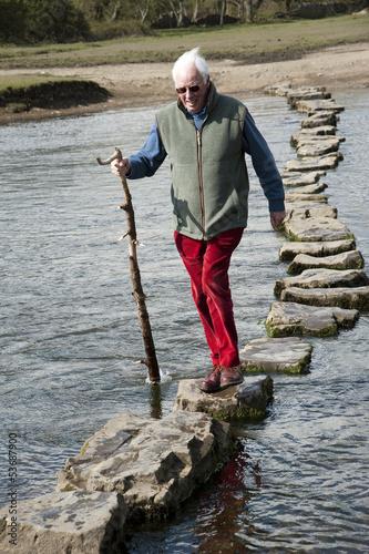 Fotografie, Obraz  Man walking on stepping stones over river