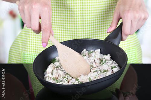 Fotografie, Obraz  Hands cooking mushroom sauce in pan in kitchen