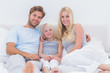 Portrait of a beautiful family in the bed