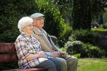 Aged Couple Sitting On A Bench In A Cemetery