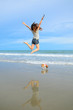 Young woman jumping with her cute jack russel puppy on the beach