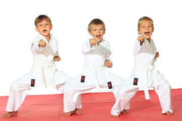 Fototapeta Sztuki walki Three children in kimono hit a punch on a white background