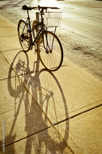 Staande foto Fiets Bicycle locked to the rack and its shadow
