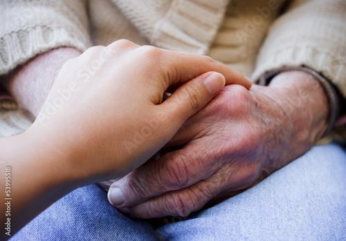 Fotografia, Obraz  Young caregiver holding senior's hands