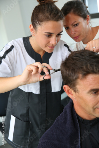 Spoed Foto op Canvas Kapsalon Student girl in hairdressing learning how to cut hair
