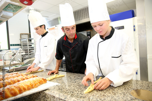 Fotografie, Obraz  Baker with students in kitchen making pastries
