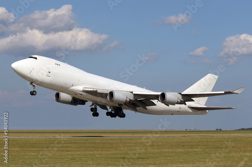 White plane taking off with clouds in the blue sky Fototapet