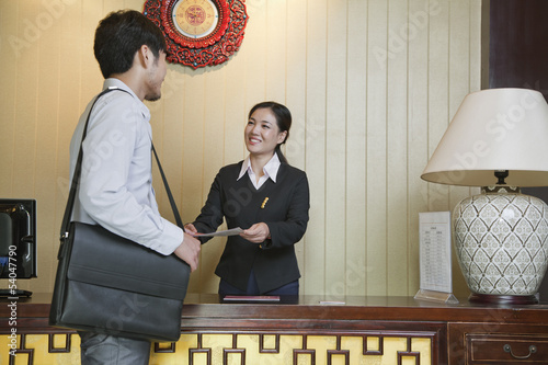Fotomural Businessman at Reception Desk of Hotel