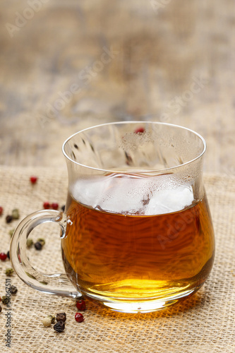 Poster de jardin Bar Glass of hot steaming tea on wooden table