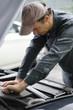Mechanic working on car motor with hood open