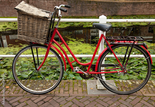 Red Bicycle with Basket Parked Beside Canal in Holland Canvas