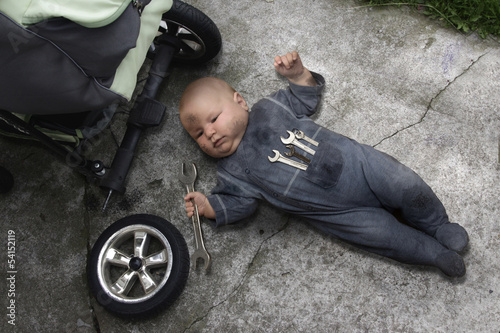 Valokuva  baby lying on the ground and repairing your stroller