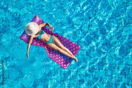 Fotografie, Obraz  Junge Frau auf der Luftmatratze im Pool