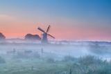 Holenderski wiatrak w gęstej porannej mgle - 54230363