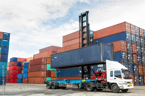 Photo Crane lifting up container in yard