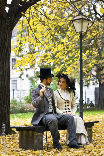 Photographie  Old-fashioned dressed couple on a park bench in fall.