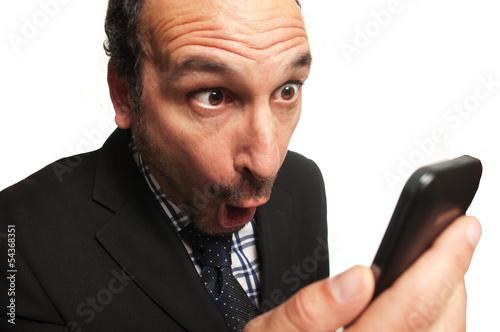 Fotografering  businessman sorpreso guardando il cellulare