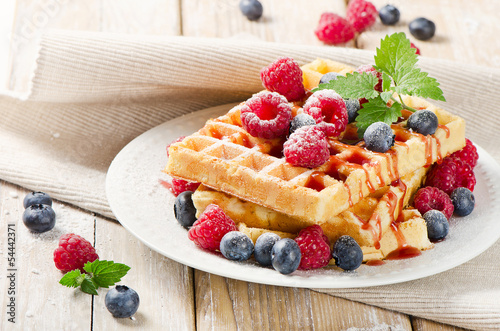Fotografía  waffles with blueberries and raspberries