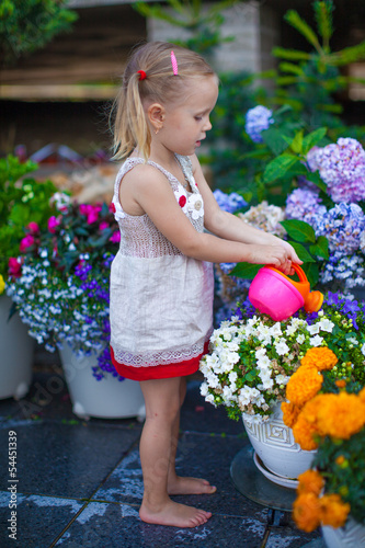 Fototapety, obrazy: Little cute girl watering flowers with a watering can