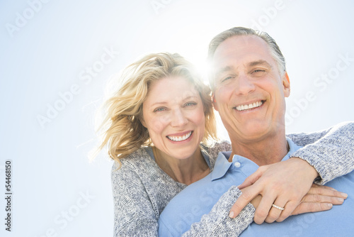 Photographie  Cheerful Woman Embracing Man From Behind Against Sky