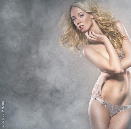 Fototapeta A young blond woman in lingerie posing on a foggy background obraz na płótnie