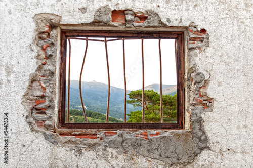 Window red bars on a white wall and demolished with forest view